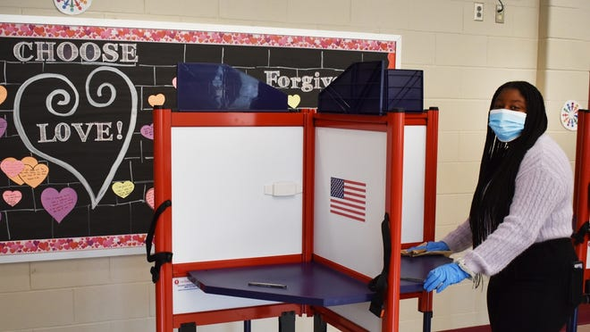 Poll worker Monique Vaz, sanitizes the voting booths at the Mary Fonseca Elementary School Tuesday. Fonseca School is the voting site of precinct 5 ward C and precinct 8 ward A.
