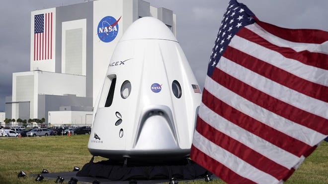 A mockup of the SpaceX crew capsule is seen on display in front of the Vehicle Assembly Building during a news conference at the Kennedy Space Center in Cape Canaveral, Fla., Friday, Nov. 13, 2020.