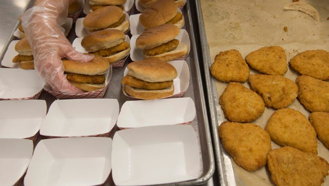 Becky Mattingly pairs baked chicken breasts with whole wheat buns for the McGary Middle School students on the first day of school Wednesday morning.