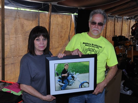 Brenda and Rich Brotherton hold a photo of their son,