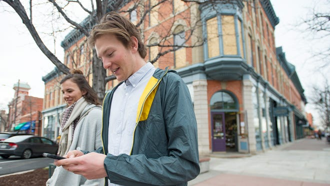 Stosh Czarniaq browses his phone while he and Kat Bush look for a place to eat in Old Town on Saturday, March 24, 2018. Cell phone carriers are looking into improving service in the area.