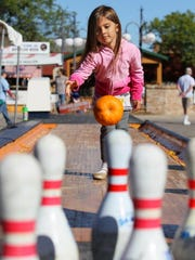 Macie Garro of Mequon age 4, tried her hand at pumpkin bowling at Harvest Fair. MICHAEL SEARS/MSEARS@JOURNALSENTINEL.COM