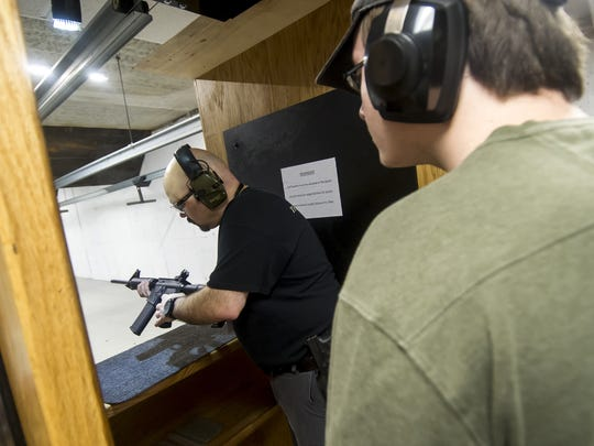 Ed Cabrera, Firearms Trainer, left, prepares a Smith