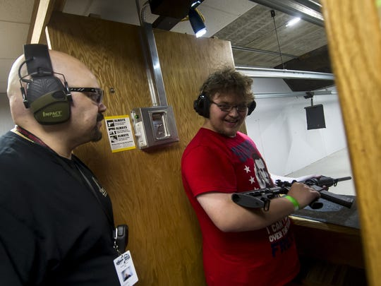 Ed Cabrera, Firearms Trainer, left and Sebastian Mongeau of Lacey, react after firing a Smith & Wesson Sport AR-15 during a free firearms training at the Union Hill Gun Club in Monroe Twp. on May 20, 2018.