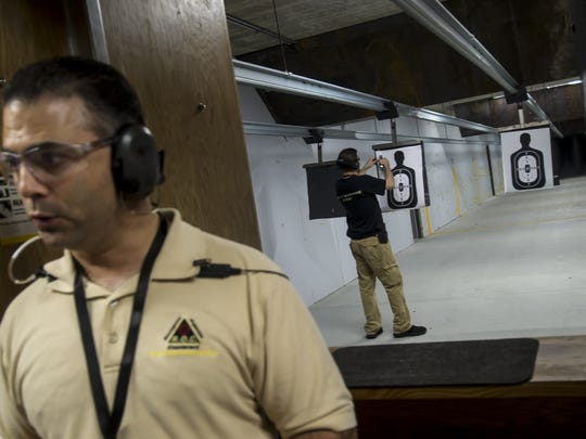 Ray Rodriguez, Firearms Trainer, prepares a target as Range Master, Rocco La Rocca II, gives instructions on firearms safety during a free firearms training at the Union Hill Gun Club in Monroe Twp. on May 20, 2018.