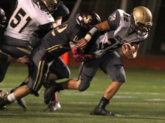 Clarkstown South's Sam Franco is tackled by Arlington's Peter Newman during their Section 1 Class AA semifinal at Arlington Oct. 27, 2017.