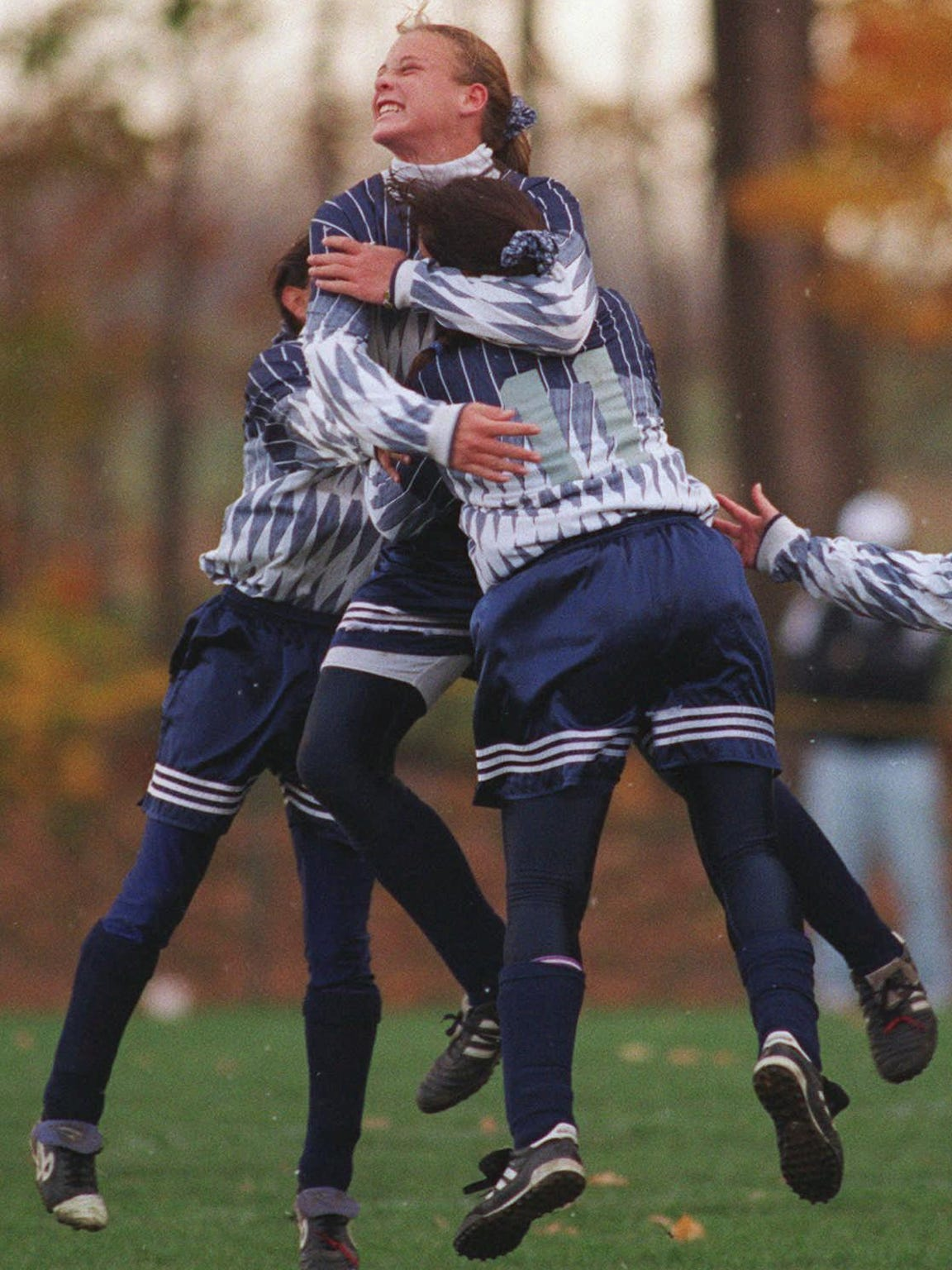 Teammates swarm Abby Wambach, center, after she scored a goal against  Greece Athena on Nov. 4, 1995. Wambach later scored on a penalty kick and saved one as a goalkeeper in the final minutes to lead Mercy to the Section V Class A championship.