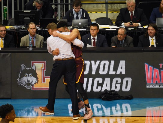 Loyola Ramblers head coach Porter Moser hugs guard