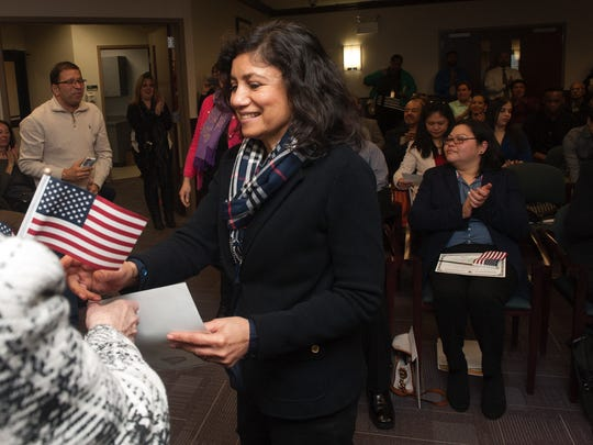 New U.S. Citizens Indira Mehta from Mount Laurel receives a U.S. flag an certificate of citizenship during the Oath of Allegiance naturalization ceremony in Mount Laurel.