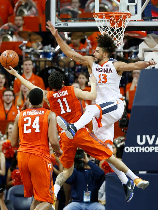 Virginia Tech forward Anthony Gill (13) blocks a shot by Virginia Tech guard Devin Wilson (11) during the second half of an NCAA college basketball game in Charlottesville, Va., Tuesday, Feb. 9, 2016. Virginia won 67-49.   (AP Photo/Steve Helber)