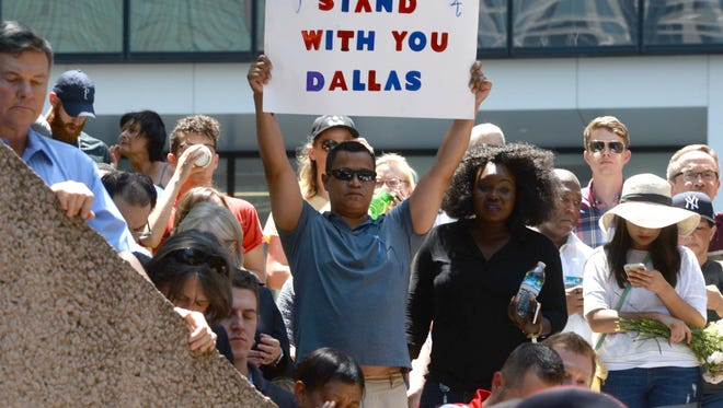 A man raises a sign to show his support for the Dallas Police Department while attending a multi-faith unity prayer service in Thanks Givings Square in Dallas Friday afternoon. The city was rocked when 5 Dallas Police Officers were killed and several more wounded at a peaceful protest Thursday evening.