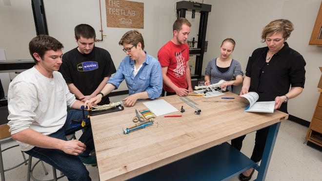 """Professors Jenni Buckley (middle, in blue) and Amy Trauth-Nare (right, in black) work with students Seth Bulich, Hunter Bachman, Kyle Culver, and Molly Wessel working on """"Orthopedics in Action"""" kits."""