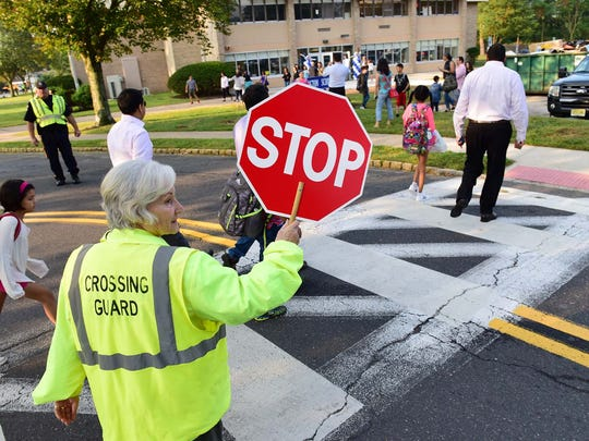 Joanne Tighe, an 18 year veteran as a crossing guard, helps children and their parents cross the street at Millburn's new school for fifth graders Tuesday morning, September 5th, 2017.