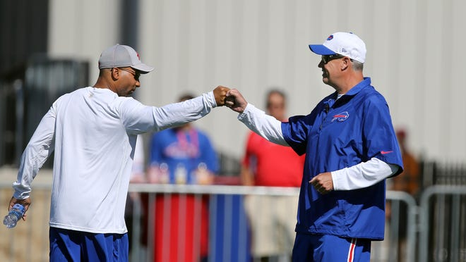 Bills head coach Rex Ryan exchanges a fist bump with general manager Doug Whaley during the first day of training camp at St. John Fisher College.