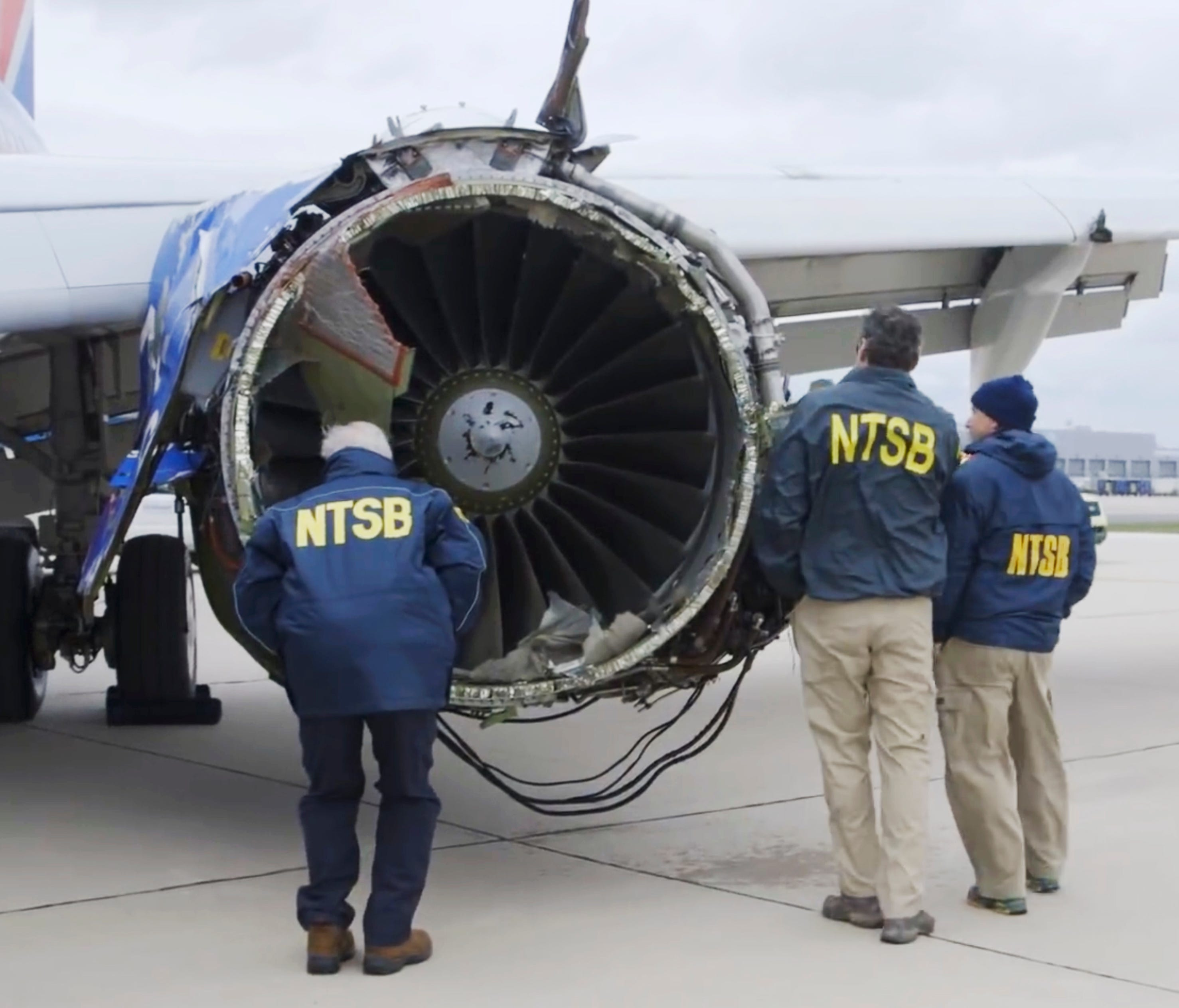 A National Transportation Safety Board investigator examines damage to the engine of the Southwest Airlines plane that made an emergency landing at Philadelphia International Airport in Philadelphia on April 17, 2018.
