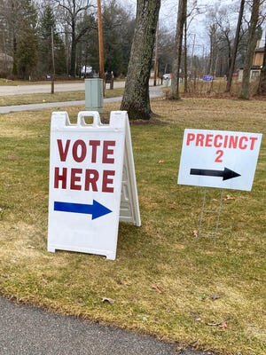 A 'vote here' sign stands outside of a voting precinct in Holland, Mich., during the March 10, 2020 election.