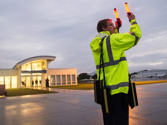 Employee at Treasure Coast International Airport  signals for airplane to land on Friday, Jan. 12, 2018 in St. Lucie County.
