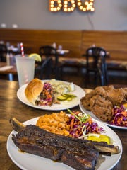 Beef rib, rubbed and smoked, with baked beans and cole slaw, center; pulled pork sandwich with smoked local pork, pickles, fresh slaw and barbecue sauce and a side of potato salad, top left; and buttermilk fried chicken that is responsibly sourced with cole slaw and corn bread at Pork & Pickles Barbeque in Essex Junction on July 13, 2016.