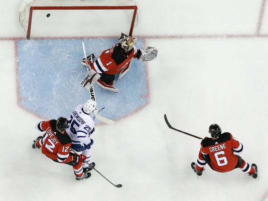 A shot by Toronto Maple Leafs center William Nylander (not shown) enters the net of New Jersey Devils goaltender Keith Kinkaid (1) during the first period of an NHL hockey game, Thursday, April 5, 2018, in Newark, N.J. Maple Leafs' James van Riemsdyk (25) attacks as Devils' Ben Lovejoy (12) and Andy Greene (6) help defend on the play. (AP Photo/Julio Cortez)