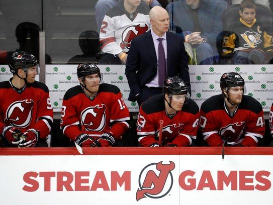 New Jersey Devils head coach John Hynes, top, looks