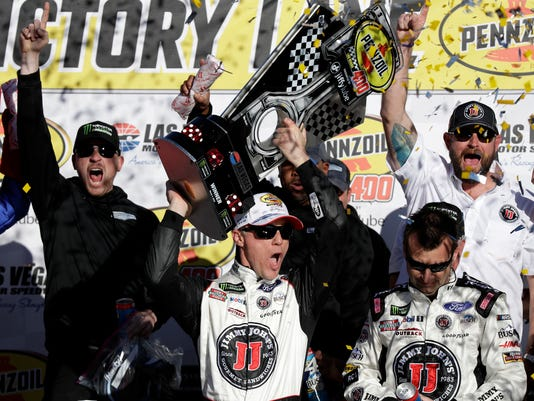 Kevin Harvick hoists the trophy with his team after winning a NASCAR Cup series auto race Sunday, March 4, 2018, in Las Vegas. (AP Photo/Isaac Brekken)