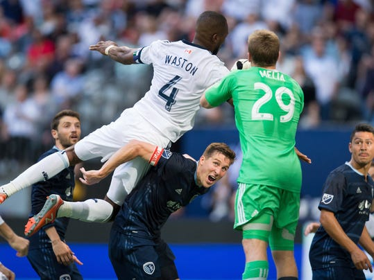 Sporting Kansas City's Matt Besler, centre, watches as goalkeeper Tim Melia (29) grabs the ball away from Vancouver Whitecaps' Kendall Waston (4) during the second half of an MLS soccer game in Vancouver, British Columbia, on Saturday May 20, 2017. (Darryl Dyck/The Canadian Press via AP)