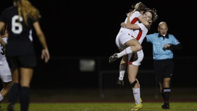 Leon's Maddie Powell is hugged by a teammate after scoring a goal on a penalty kick against Navarre during their Region 1-4A quarterfinal on Thursday. The Lions won 4-3 in double OT on Liney Brantley's game-winner.