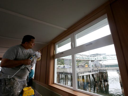 David Rinci looks out the window at the WSF dock as he caulks parts of the ceiling of the fast ferry dock walkway at the Port of Kingston on Tuesday, July 10, 2018.