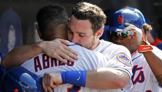 The Mets' Daniel Murphy, right, hugs Bobby Abreu after scoring on a hit by Lucas Duda during the fifth inning against the Houston Astros on Sunday. Abreu had been removed for a pinch runner after hitting a single in his last at-bat in the majors. The Mets defeated the Astros 8-3.
