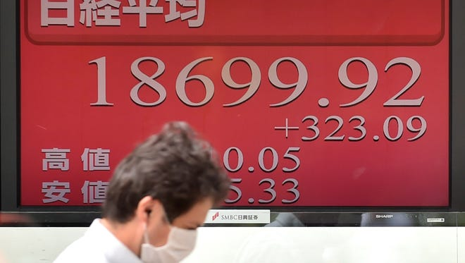A pedestrian walks past a board showing numbers for the Tokyo Stock Exchange in Tokyo on August 27, 2015.
