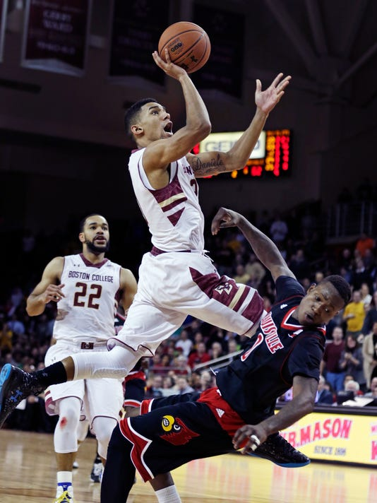 Boston College guard Olivier Hanlan (21) drives to the basket as he is fouled by Louisville guard Terry Rozier (0) during the second half of an NCAA college basketball game in Boston, Wednesday Jan. 28, 2015.  Louisville defeated Boston College 81-72. (AP Photo/Charles Krupa)
