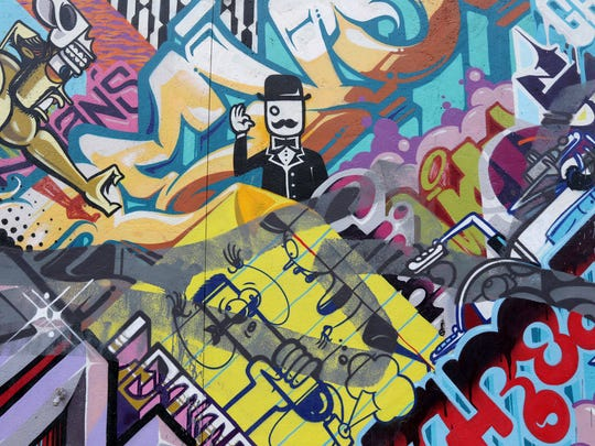 "A detail from ""A Man's Threat & a Woman's Pet,"" a mural by Revok and Rime at 1501 Division in Eastern Market."