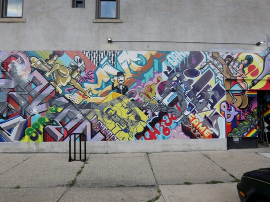 """A Man's Threat & a Woman's Pet,"" a mural by Revok and Rime at 1501 Division in Eastern Market."