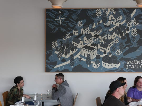 A large blue painting by James Noellert depicting the town of Supino, Italy, is a focal point in the spare dining room at La Rondinella in Detroit's Eastern Market.