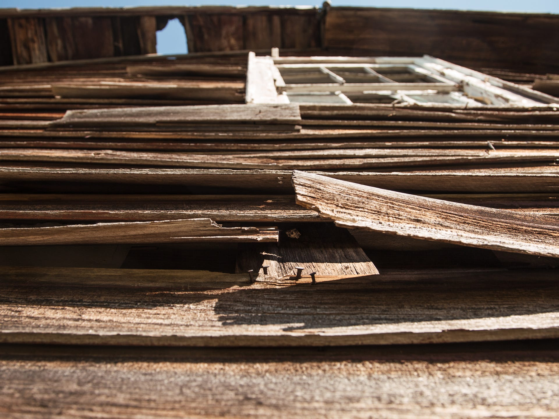 Weather-warped wood peels away from an empty house