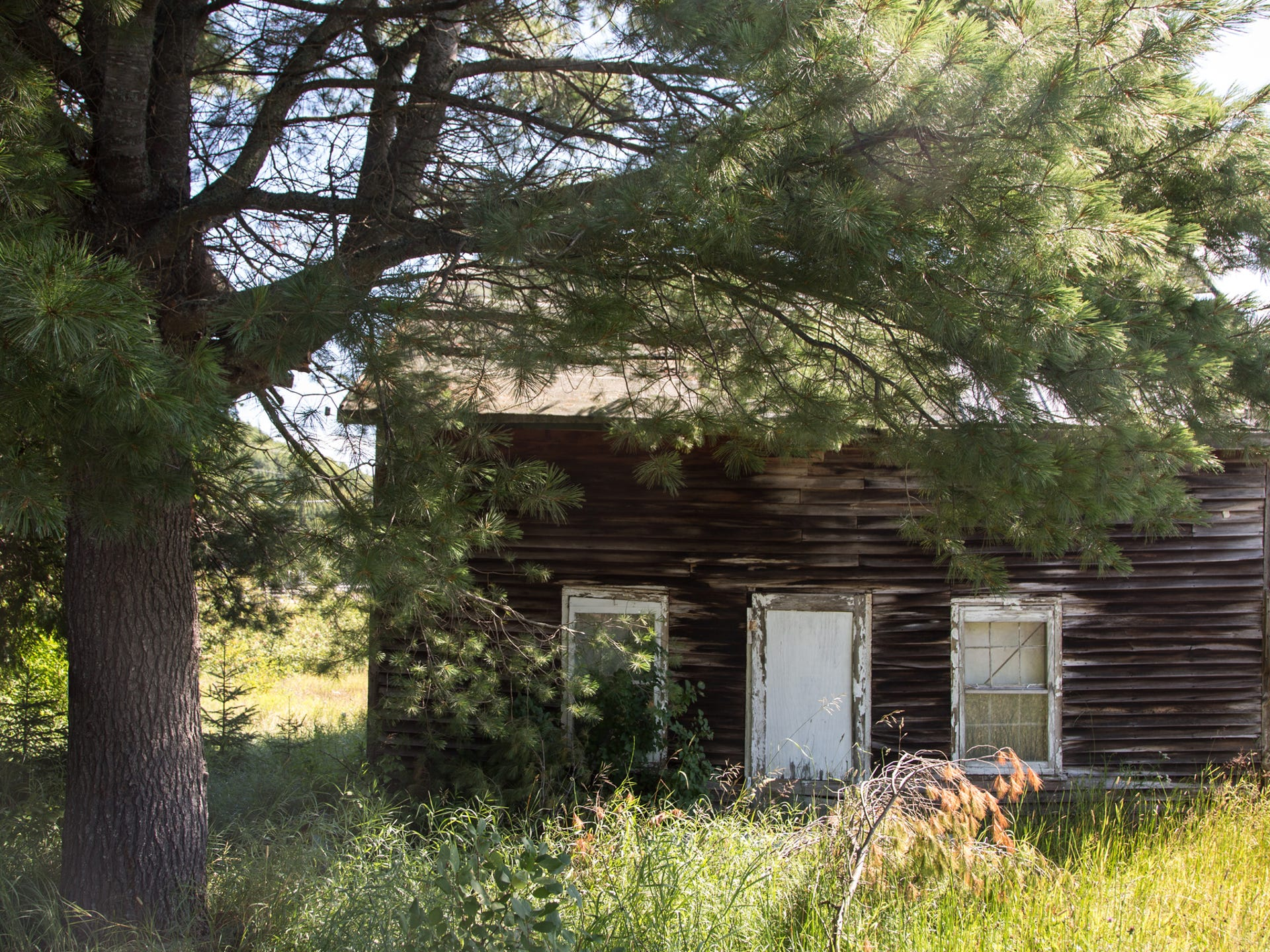 An empty miner's shack sits along a quiet highway in