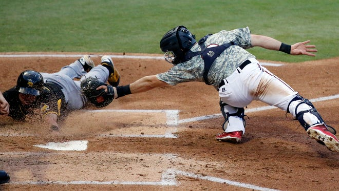 El Paso Chihuahuas catcher to Austin Hedges makes the tag at home plate as Salt Lake Bees catcher Juan Graterol attempts to beat the throw.