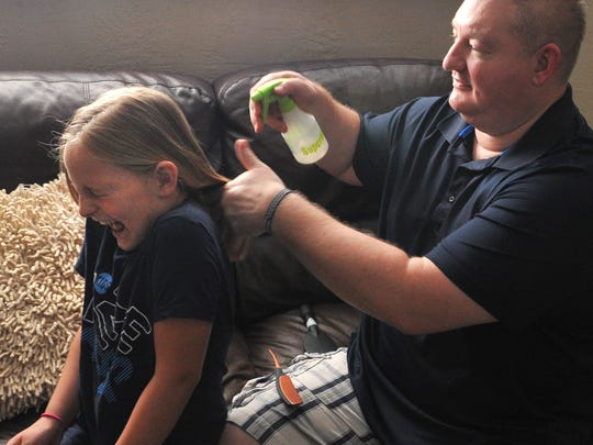 Doug Marquardt, right, prepares to style his daughter Adalyn's hair. Marquardt says he started styling Adalyn's hair after watching how-to videos on the internet.