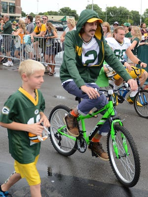 Tom Wrigglesworth, known as a Green Bay Packers quarterback Aaron Rodgers look-alike, rides a bike during Packers training camp on Aug. 25.