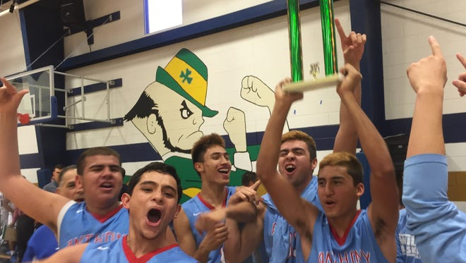 The Anthony Wildcats celebrate after defeating the Cathedral Fighting Irish, 64-53, on Saturday in the championship game of the Cathedral Basketball Tournament.