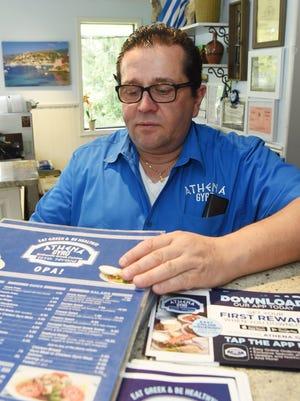 Georgics Maravegias, 53, owner of Athena Gyro in LaGrangeville, looks through some menus at the front counter.