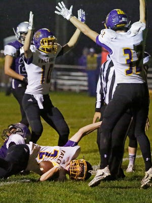 Sheboygan Falls' Ethan Plier (27) grips the football as his fellow Falcons celebrate a touchdown Friday against Kiel.