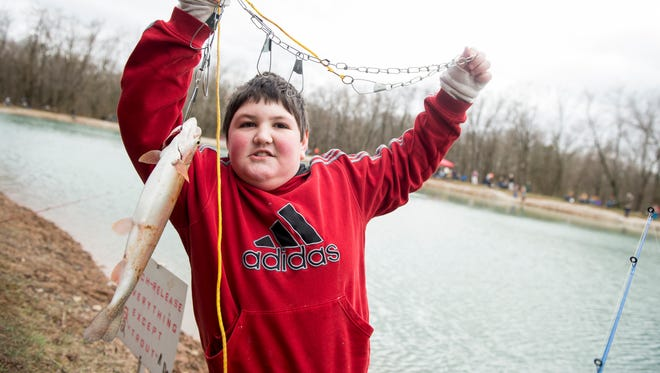 Eric Berkheimer, 12, holds up a trout he caught while fishing at Kaiser Lake in New Oxford during the first day of trout season on Saturday. The McSherrystown Fish and Game Association sponsored the free, youth only, trout fishing day at the lake.