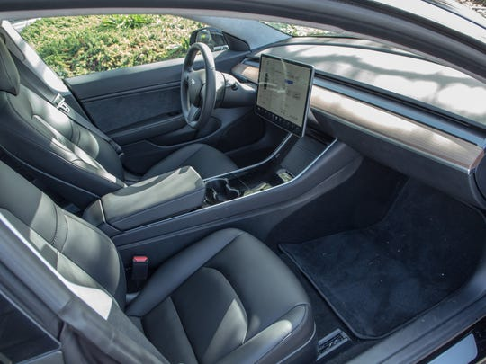 The interior of the Tesla Model 3 is stark, with few buttons and a single