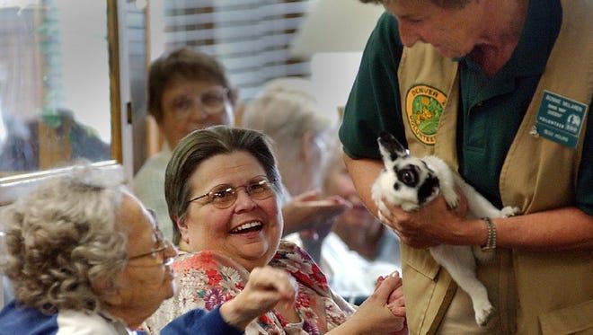 Denver Zoo volunteer Bonnie McLaren, right, shows a rabbit to visitors.