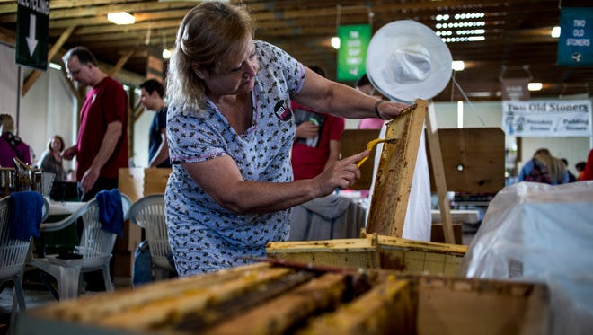 Sue Hunt-Case, of St. Clair, prepares honeycomb for honey extraction at the Pine River Beekeeping Club booth during the Earth Fair Friday, April 28, 2017 at Goodells County Park.