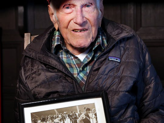 This Jan. 21, 2014 photo provided by USC Dornsife College of Letters, Arts and Sciences, Louis Zamperini displays one of his photographs as a student and sprinter, at his Los Angeles home. Zamperini, a U.S. Olympic distance runner and World War II veteran who survived 47 days on a raft in the Pacific after his bomber crashed, then endured two years in Japanese prison camps, died Wednesday, July 2, 2014, according to Universal Pictures studio spokesman Michael Moses. He was 97.