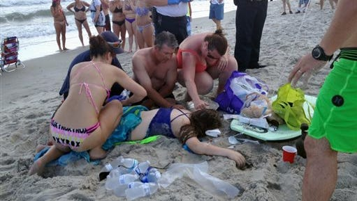 Emergency responders assist a teenage girl at the scene of a shark attack in Oak Island, N.C. on Sunday. Mayor Betty Wallace of Oak Island, a seaside town bordered to the south by the Atlantic Ocean, said that hours after the teenage girl suffered severe injuries in a shark attack Sunday a teenage boy was also severely injured.