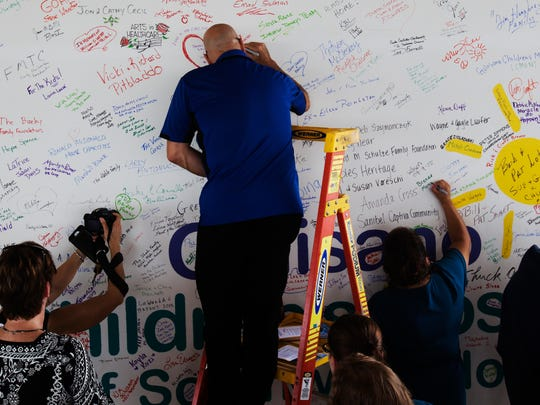 Lee Memorial Health System employees and local dignitaries sign a wall during a topping off ceremony at the Golisano Children's Hospital of Southwest Florida on Wednesday.  The hospital is set to open in 2017.