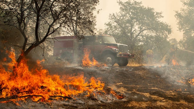 Firefighters battling the Carr fire douse a hot spot near Redding, Calif. The blaze has grown to 140 square miles and is only 5 percent contained.